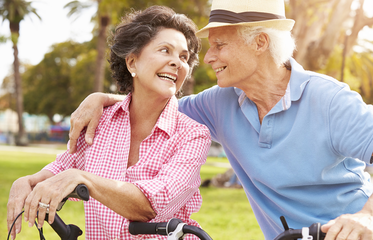 A senior man and woman riding bikes together outdoors