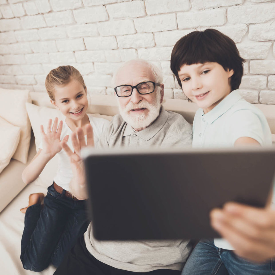 Photo of senior man with girl and boy grandkids looking at electronic device