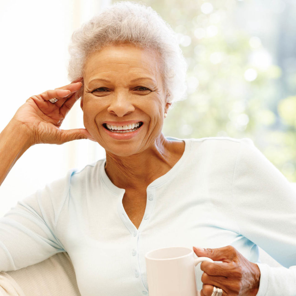 senior african american woman inside with a cup of coffee