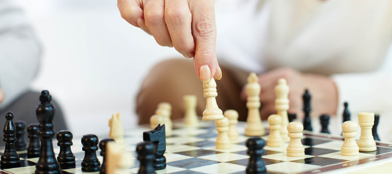 photo of a female hand moving a chess piece during a game