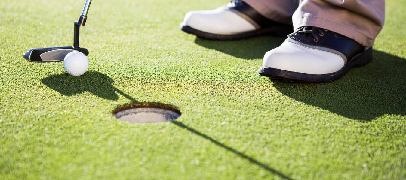 photo of golfer's feet putting golf ball into hole