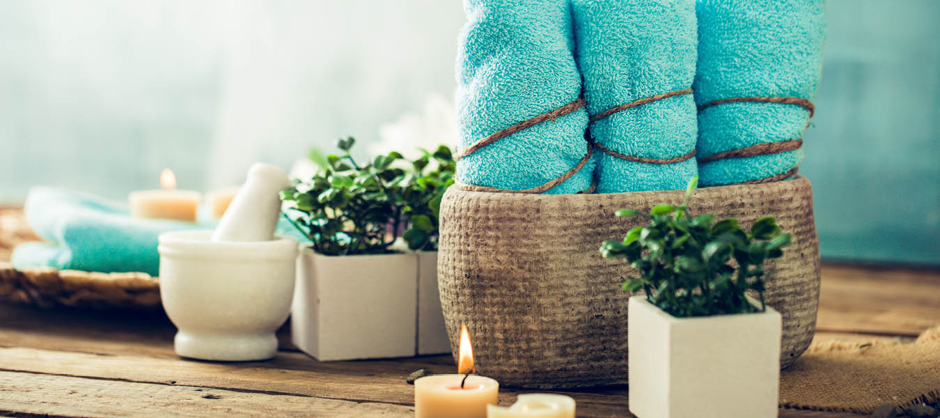 Spa accessories of towels in basket, plants and burning candles