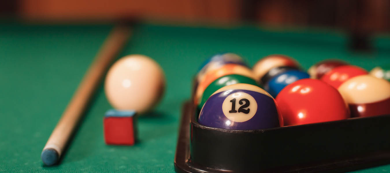 Close up billiard table with cue, chalk cube, and racked balls