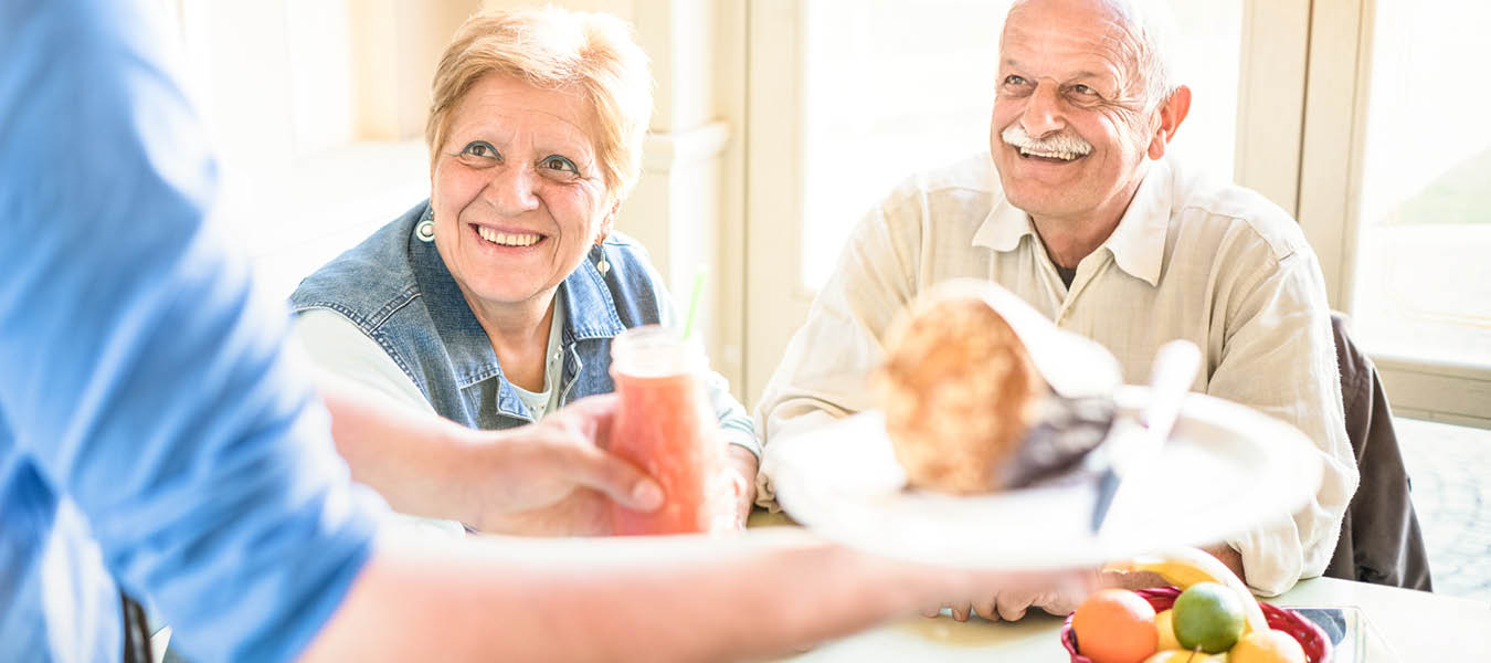 Smiling senior male and female couple waiting on server to deliver food