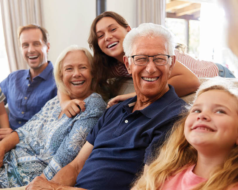 family photo of senior couple with son and granddaughters sitting on a couch