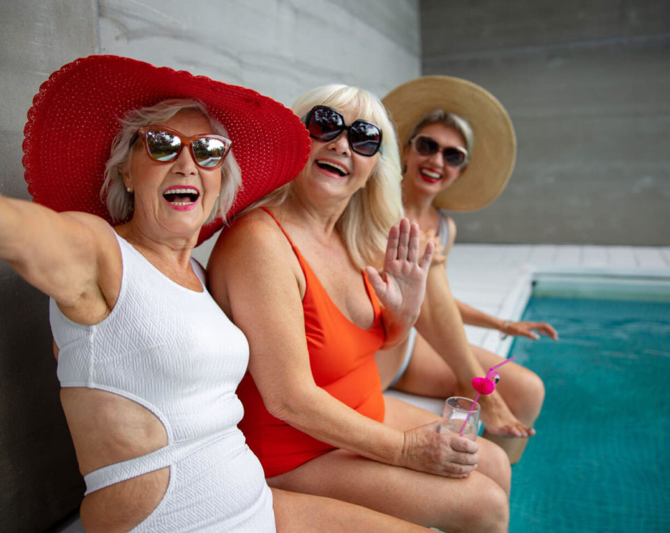 Photo of three women in swimsuits by the pool