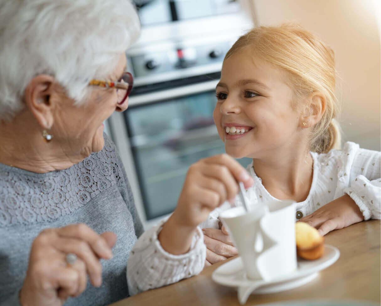 Photo of grandma and granddaughter at table sharing a hot drink